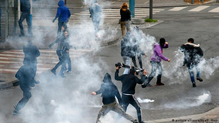 Young people run from tear gas police sprayed to quell protests in Bobigny
