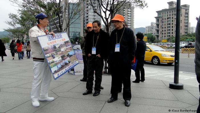 A Falun Gong activist (left) holds up a protest sign in front of visitors from mainland China