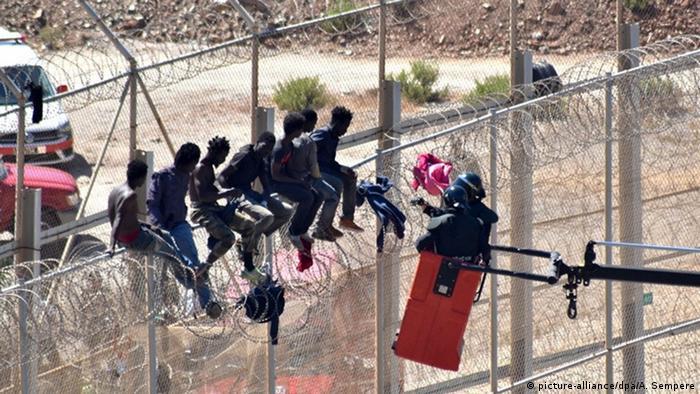 Refugiados sentados em cima de uma cerca em Ceuta