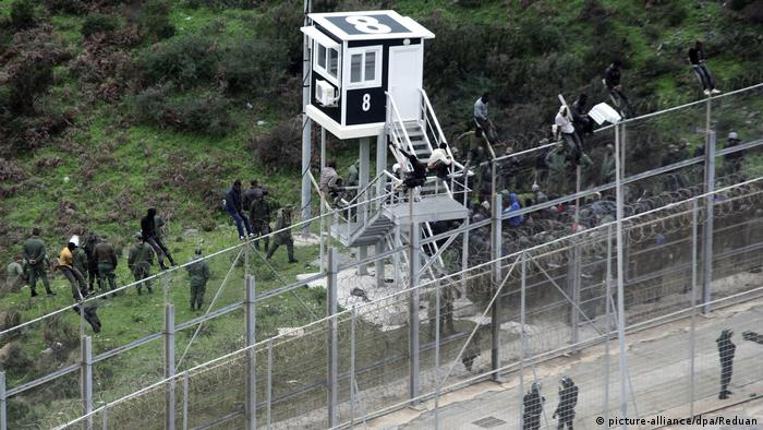Moroccan Police look at immigrants trying to jump the six-meter-high fence in Ceuta, Spanish enclave on the north of Africa (picture-alliance/dpa/Reduan)