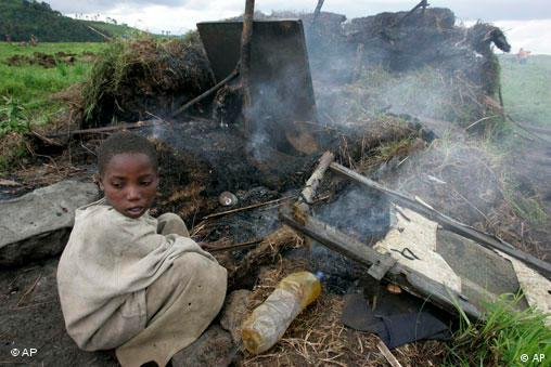 A displaced child returns to the ruins of a hut that was destroyed last week during fighting at a camp for displaced people which was evacuated in Kibumba