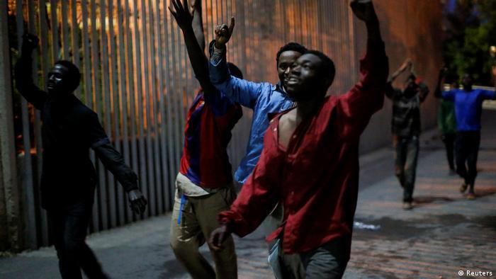 Inmigrantes subsaharianos entran a Ceuta tras saltar una valla fronteriza.