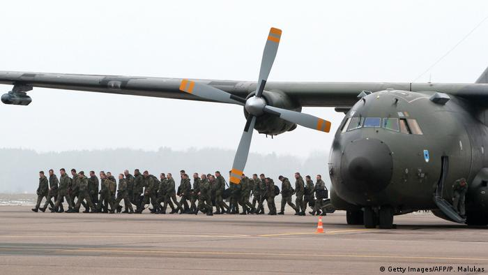 German soldiers walk over tarmac away from a transport plane