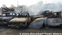 People stand behind burnt out cars following an attacked at a car park in Maiduguri, Nigeria, Friday, Feb. 17, 2017. Battling multiple bombers strapped with suicide vests, Nigerian troops and civilian self-defense fighters repelled the fiercest Boko Haram extremist attack in months on the key northeastern city of Maiduguri on Friday. (AP Photo/Hamza Suleiman) |