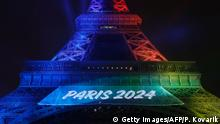 TOPSHOT - A picture shows the Eiffel Tower lit in the colours of the Olympic flag during the launch of the international campaign for Paris' bid to host the 2024 Olympic Games, on February 3, 2017, in Paris. / AFP / Patrick KOVARIK (Photo credit should read PATRICK KOVARIK/AFP/Getty Images)