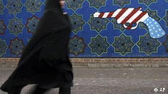 An Iranian woman walks passed an anti-American mural outside of former U.S. embassy in Tehran