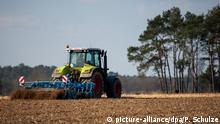 Tractor running over cropland in Germany (picture-alliance/dpa/P. Schulze)