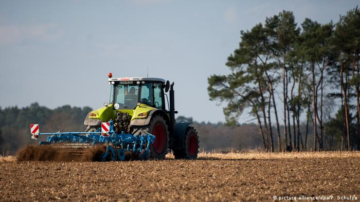 Tractor running over cropland in Germany