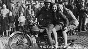 Ein Soldat sitzt mit zwei jungen Frauen auf seinem Motorrad.