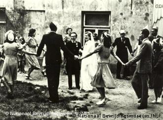 Inmitten einer Hausruine tanzen Leute um ein Hochzeitspaar herum.