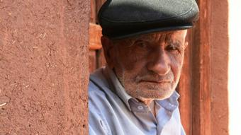 Ein alter Mann mit Baskenmütze steht neben einer Wand