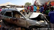 19.02.2017 *** Civilians stand near a car destroyed in a suicide bomb explosion at the Wadajir market in Madina district of Somalia's capital Mogadishu, February 19, 2017. REUTERS/Feisal Omar