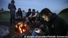 Refugees and migrants try to warm themselves through fires in the makeshift camp in Idomeni