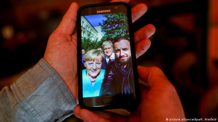 Mobile phone with photo of Angela Merkel with asylum seeker Rodin Saouan