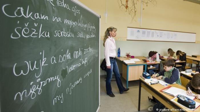 Professora diante da lousa e alunos em aula de sórbio com Cottbus, no leste da Alemanha