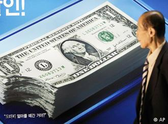 A South Korean man walks past in front of a poster featuring a stack of dollars