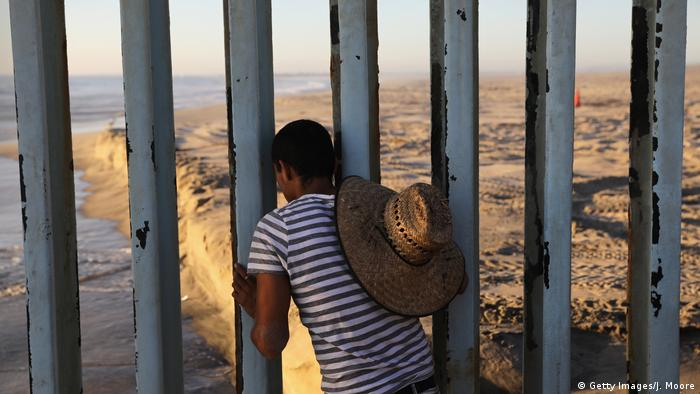 A man looks through the U.S.-Mexico border fence into the United States (Getty Images/J. Moore)