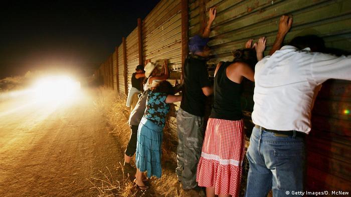 Pessoas numa cerca na fronteira entre os Estados Unidos e México em Campo, perto de San Diego