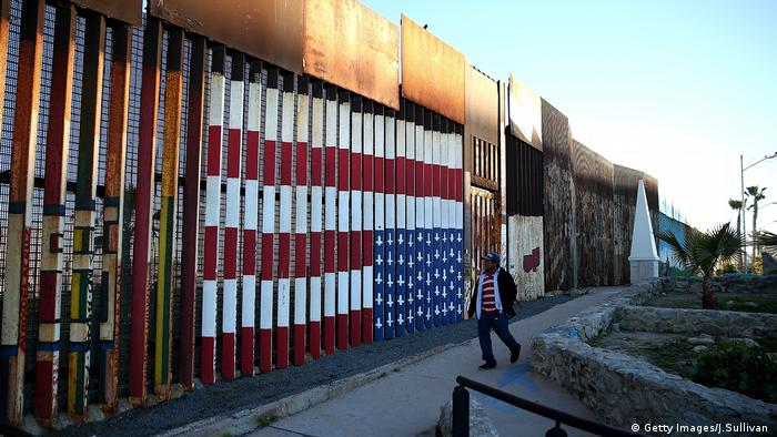 An upside-down, backwards, US flag is painted on the Mexican side of the exisitng wall between the US and Mexico.