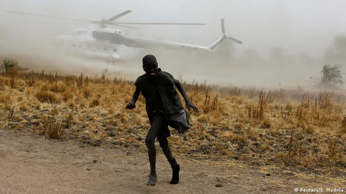 Boy and aid helicopter in South Sudan