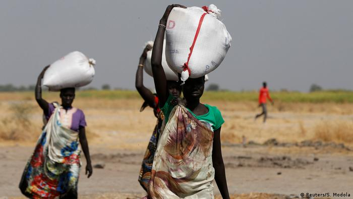 South Sudanese women carrying sacks of food