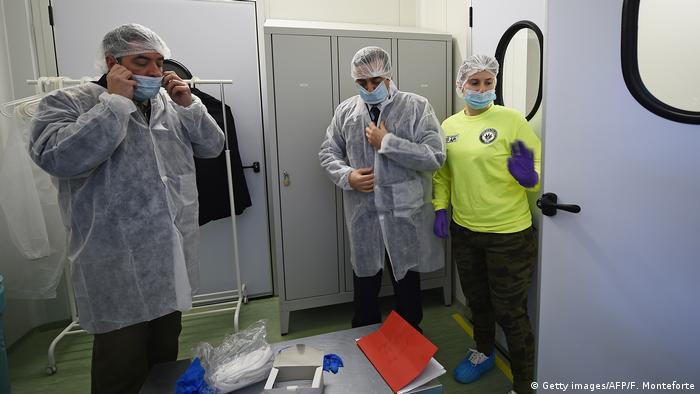 Três pessoas vestem roupas especiais para entrar no laboratório de cultivo de maconha