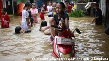 21.02.2017 *****Mädchen sitzen am 21.02.2017 auf einem Roller in einer überfluteten Straße in Jakarta (Indonesien). Sintflutartiger Regen hat zu Hochwasser in teilen der indonesischen Hauptstadt geführt. Foto: Dita Alangkara/AP/dpa +++(c) dpa - Bildfunk+++  