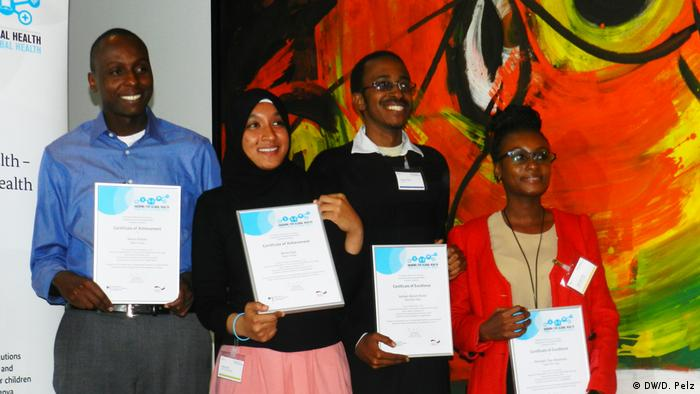Five participants of the competition smiling and holding their certificates of excellence and of participation respectively.