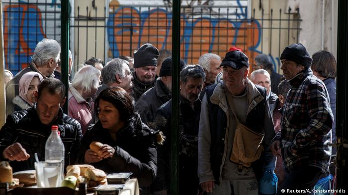 People line up as they wait to enter a soup kitchen in Athens.