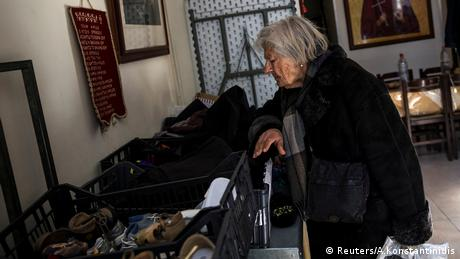 An elderly woman searches through donated clothes at a soup kitchen.