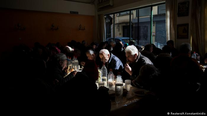 People eat at a soup kitchen in Athens.