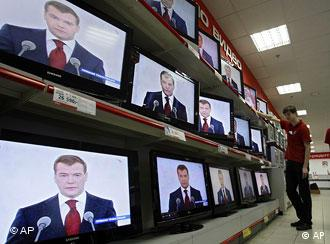 Shop assistants watch Russian President Dmitry Medvedev making the address to the nation at a Moscow shop