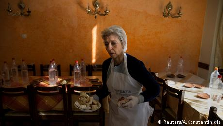 Retired teacher and volunteer Eva Agkisalaki clears tables at a soup kitchen run in Athens.