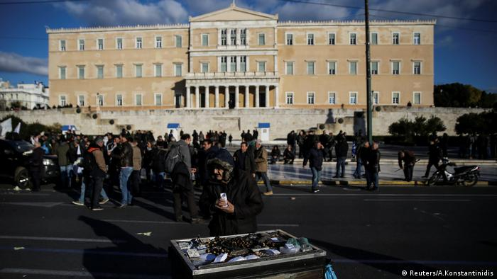 An elderly man sells chestnuts in front of the parliament during a demonstration to demand tax reductions and compensations in Athens.
