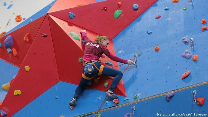 Альпинист с надписью Россия на альпинистской стенке с красной звездой
