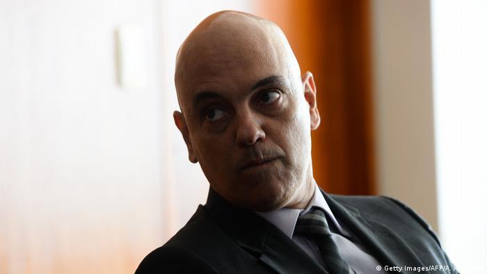 Foto mostra o rosto de Moraes, olhando para o lado, sério, Ele usa terno escuro.