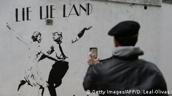 Mural in London by English street artist Bambi depicting British Prime Minister Theresa May dancing with US President Donald Trump under the words lie lie land