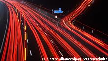 Line of car lights on an autobahn at night (picture alliance/dpa/J. Stratenschulte)