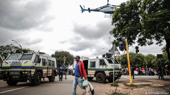 A man carrying groceries walks past police vehicles during a stand-off between Somali migrants and anti-immigrant protestors in Pretoria