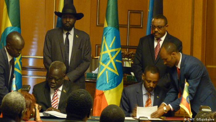 Salva Kiir Mayardit and Ethiopia's prime Minister Hailemariam Desalegn look over as officials sign peace agreement