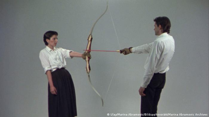 Marina Abramovic and Ulay standing opposite each other while holding the two ends of a bow directed against her. (Ulay/Marina Abramovic/Bildupphovsrätt/Marina Abramovic Archives)