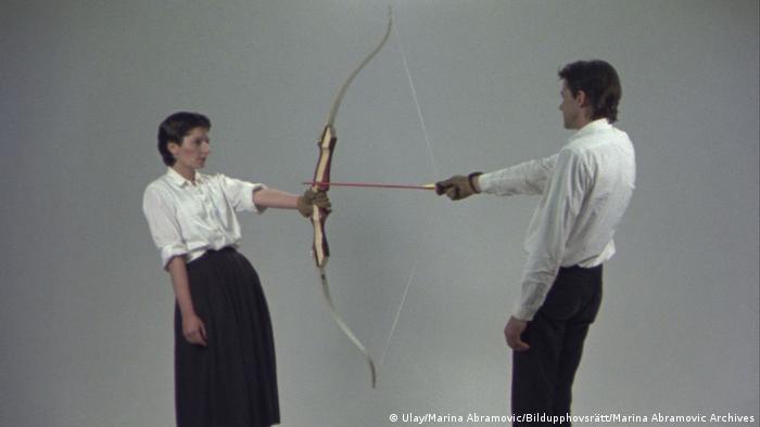 Marina Abramovic und Ulay stehen sich gegenüber und halten jeweils eine Seite eines Bogens in der Hand. Der Pfeil ist auf sie gerichtet, er spannt die Sehne des Bogens. (Ulay/Marina Abramovic/Bildupphovsrätt/Marina Abramovic Archives)