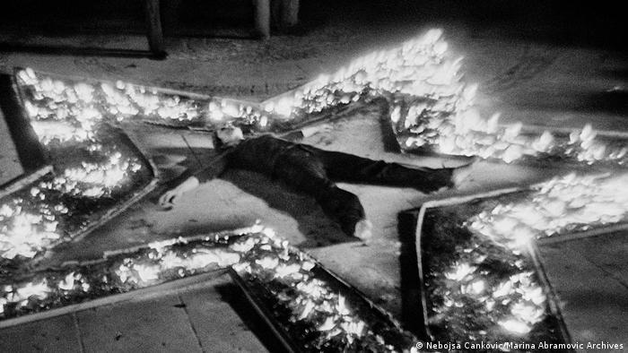 Marina Abramovic liegt, Arme und Beine von sich gestreckt, bei ihrer Performance Rhythm 5 in der Mitte eines brennenden Sterns auf dem Boden. (Nebojsa Cankovic/Marina Abramovic Archives)