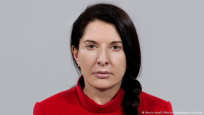 A portrait of Marina Abramovic looking into the camera. Her hair is plaited, and she wears a red shirt. (Marco Anelli /Marina Abramovic Archives)