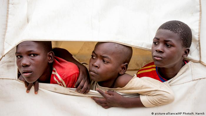 Three young refugees look out of their tent at a camp in northern Cameroon