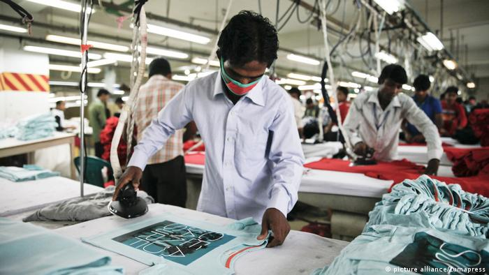 Workers iron T-shirts before they are packaged at a Bangladeshi factory