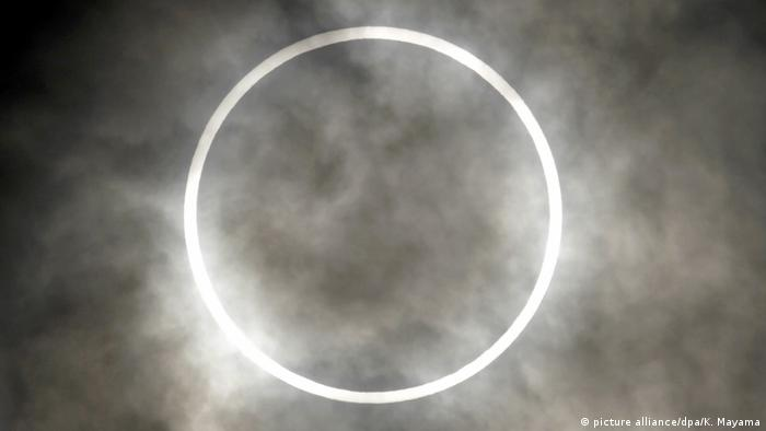 A ring-shaped annular solar eclipse behind clouds.