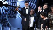 26.02.2017+++ 89th Academy Awards - Oscars Awards Show - Hollywood, California, U.S. - 26/02/17 - Writer and Director Barry Jenkins of Moonlight holds up the Best Picture Oscar in front of host Jimmy Kimmel (rear) as he stands with Producer Adele Romanski (R). REUTERS/Lucy Nicholson