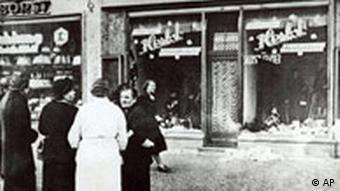 Passanten stehen am 10. November 1938 vor der eingeschlagenen Schaufensterscheibe eines jüdischen Geschäfts (Foto: AP)