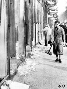 A youth with a broom prepares to clear up the broken window glass from a Jewish shop in Berlin, the day after the Kristallnacht rampage